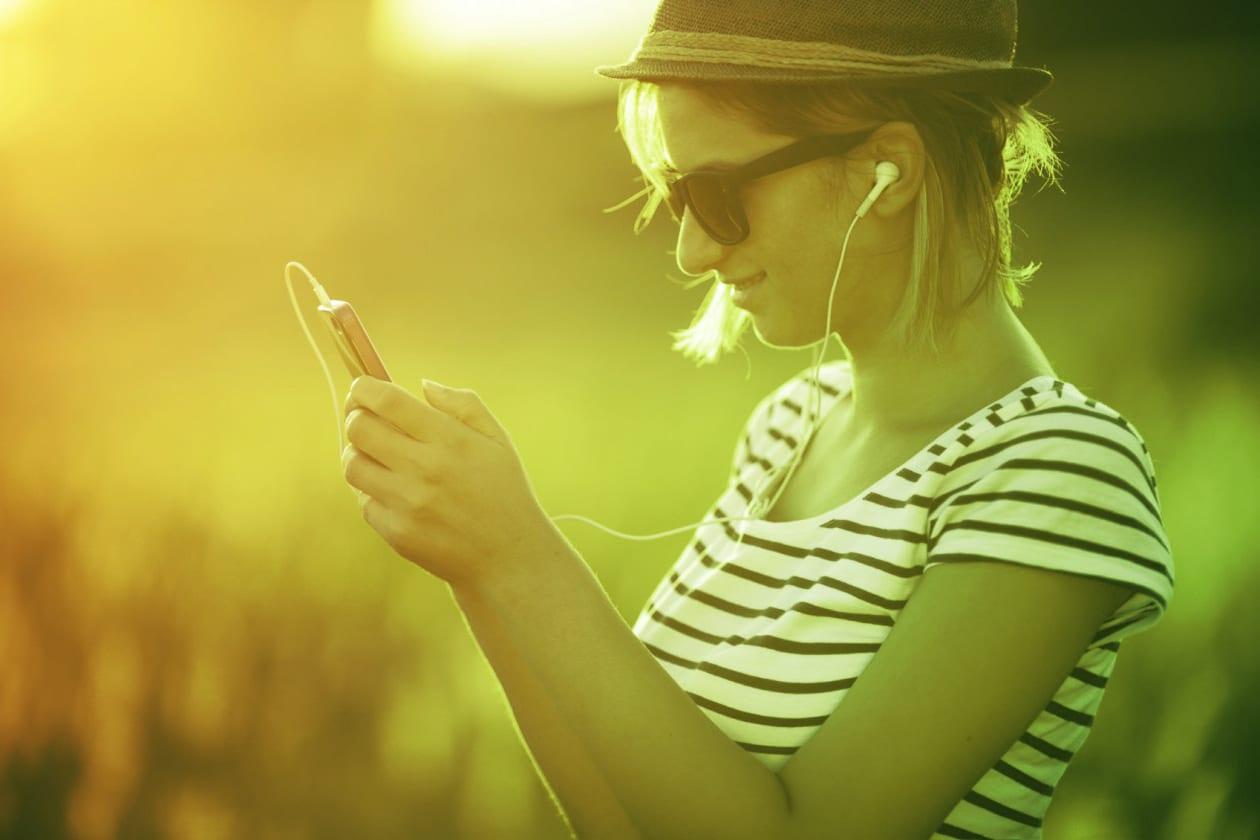 Woman using earphones to listen to radio on phone